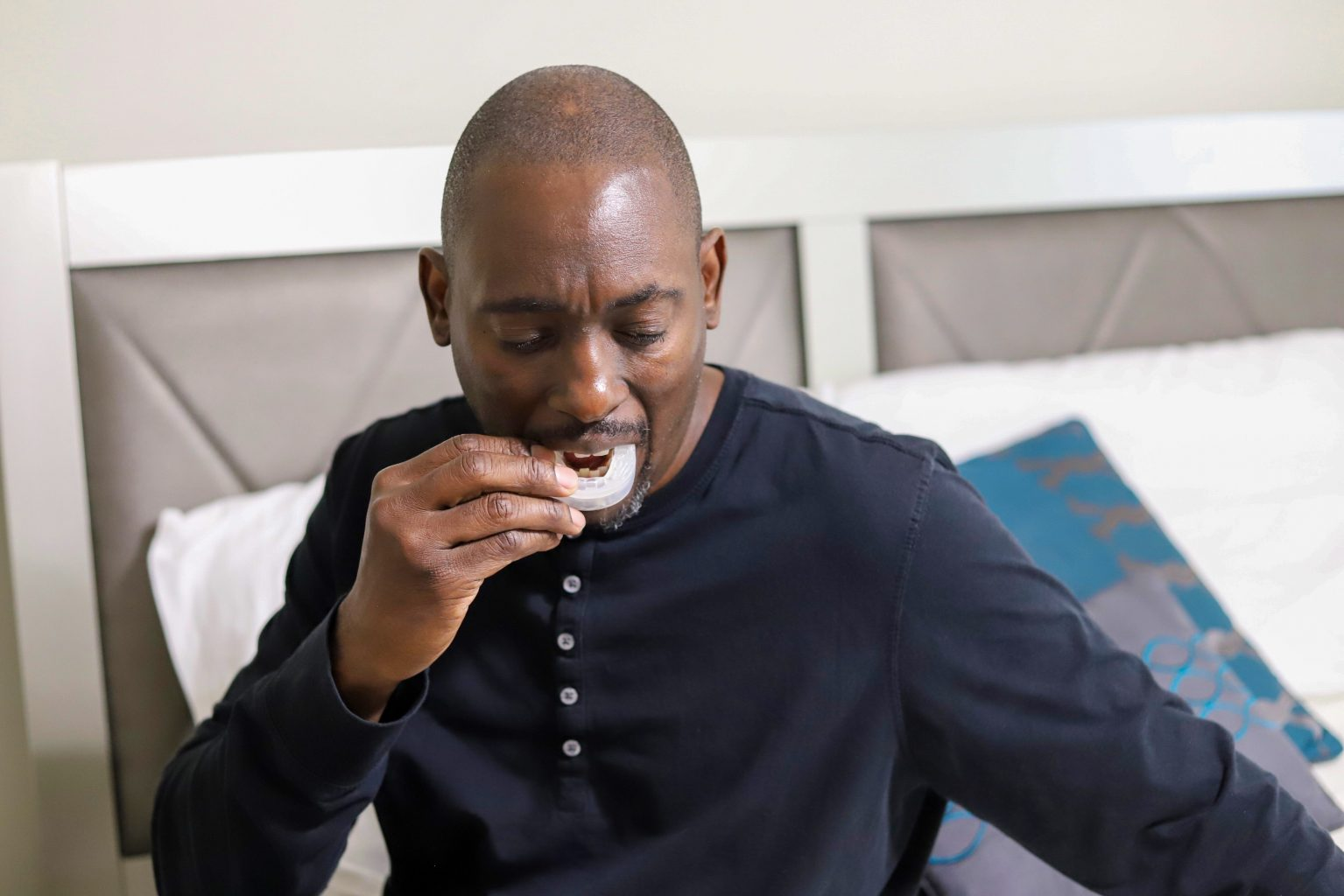 a portrait of an african american man using a snore mouth guard before bed